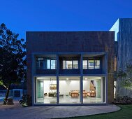 View from garden to contemporary house with illuminated interior at twilight