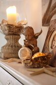 Atmospheric arrangement of candles, cherub and stone-based candle lantern