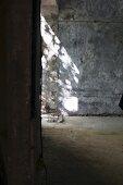 Lichteinstrahlung auf graue Betonwand eines leerstehenden Raumes