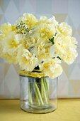 Double yellow tulips in glass vase