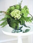 Bouquet of ferns and hydrangeas on glass table