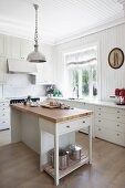 Free-standing island counter in white, wood-clad, country-house kitchen