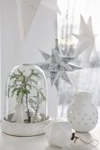 White Christmas arrangement with fir branch under glass cover