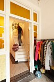 Coat rack next to lattice door in hallway and man walking up white wooden staircase in rustic stairwell