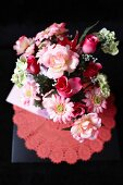 Bouquet of roses and gerbera daisies in various shades of red on doily
