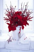A red winter arrangement of holly berries, amarillis and poinsettias