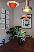 Various, retro-style pendant lamps above vase of flowers on dining table and classic chairs; framed pictures on wall