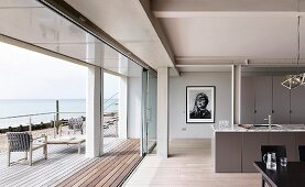 Open-plan kitchen with dining area in beach house with wooden terrace and view of sea