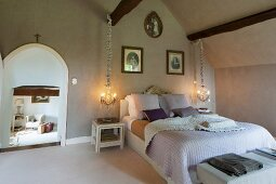 Rustic bedroom with lit pendant lamps flanking double bed and open arched doorway to one side