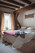 Wood-beamed ceiling, scatter cushions and counterpane arranged on bed and striped wallpaper in bedroom