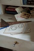 Spectacles and hand-written papers on white-painted writing desk