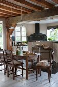 Carved chairs at dark wooden dining table in open-plan kitchen of old country house