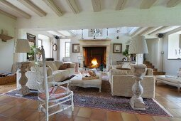 Carved chair with tall backrest, magnificent standard lamps and pale sofa set in open-plan interior with large fireplace