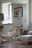 Rococo armchair with pale cover and side table with turned and carved pedestal base below chandelier with glass pendants