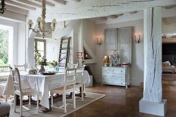 White chairs with carved backrests, table with white tablecloth and whitewashed supporting structure in dining area of old country house next to window