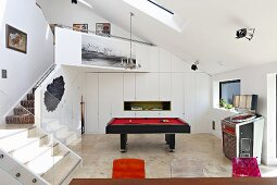 Pool table in open-plan games area and staircase leading to gallery in contemporary building
