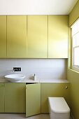 Green fitted cupboards and white countertop basin in bathroom