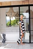 Young woman in dress with block strips in front of free-standing bathtub