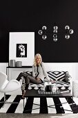 Young woman in a black and white living room with graphic patterns