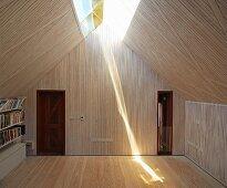 Raum mit Holzverkleidung und Oberlichtband in Dachschräge, strahlende Lichtreflexion auf Dielenboden