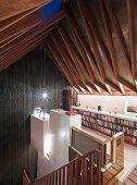 Galerieebene mit außergewöhnlicher Dachkonstruktion, weißem kubischem Einbau und hoher holzverkleideter Giebelwand