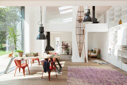 Black pendant lamp in dining area next to glass wall in open-plan interior with gallery and fitted shelving