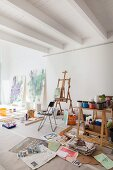 Pots of paint on workbench and easel in bright studio