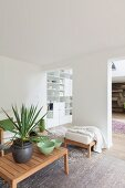 Houseplant and ceramic bowl on wooden coffee table in open-plan white living area with open doorways