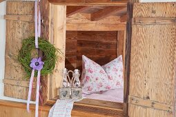 Wreath of bilberry stalks and anemone hung from open shutter and view of pillow on bed through open window