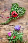 Spring arrangement of bilberry stems tied into love-heart and red anemone