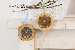 Embroidered wooden discs hung from branch as Easter decorations