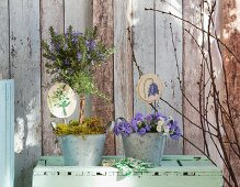Embroidered plant-pot ornaments in planted zinc pots against vintage wooden wall