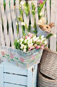 Tulips in embroidered bicycle basket on top of wooden crate painted pale blue