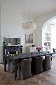 Um dunkelbraunen, massiven Holz-Esstisch mit gedrechselten Tischbeinen, Polsterstühle in passendem Farbton, oberhalb Designer-Pendelleuchte mit Lampenschirm aus Perlmuttplättchen