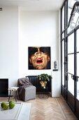Grauer Polstersessel und Beistelltisch vor Wand mit Fotokunst, seitlich Terrassentür mit Metallrahmen und Glasfüllung