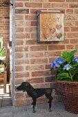 Rustic letterbox on brick façade above black, dachshund-shaped boot scraper
