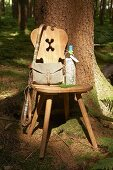 Hiking accessories and wine bottle wrapped in map on wooden chair with carved backrest below tree in woods