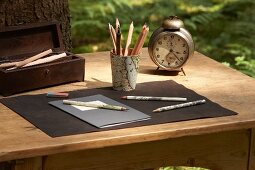 Pen holder covered in map and old alarm clock on wooden table outdoors