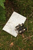 Old pair of binoculars and map on mossy ground