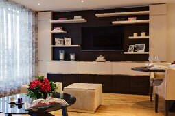 Fitted cabinets with integrated flatscreen TV in classic, elegant interior with velvet-covered pouffes