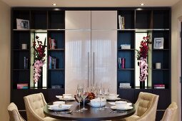 Fitted cupboards with shelves, closed fronts and elegant flower arrangements in mirrored niches behind set table with velvet armchairs