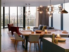 Open-plan living area with spherical glass lamps and glass walls in penthouse apartment