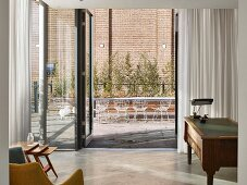 Open glass wall in study with English desk leading to roof terrace with retro wire mesh chairs