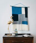 A knitted wall hanging made from a mixed woollen yarn in a block print