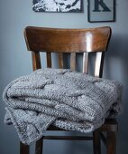 A grey blanket with a cable knit pattern on a wooden chair