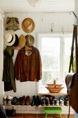 Jackets and hats hung from coat pegs on white wooden wall above full shoe rack below window