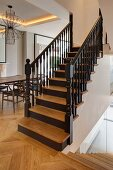 Restored wooden staircase in open-plan living area with classic chairs and exotic-wood parquet flooring