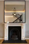 Mirror on white mantelpiece reflecting staircase and designer lamp in renovated interior