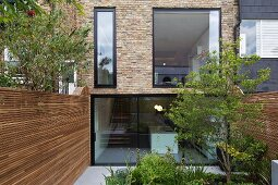Modernised façade of old terrace house with glass wall and garden between wooden screens