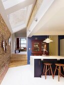 Open-plan kitchen with white tiled floor, modern strip of skylights, brick walls and view into living area